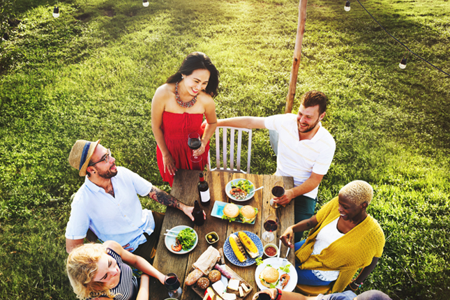 A group of friends having an outdoor meal together on their lawn.
